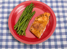 Baked Salmon and Asparagus on Red Plate Royalty Free Stock Image
