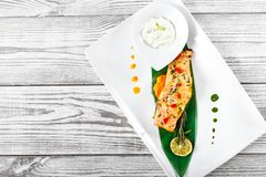 Baked salmon with cheese sauce, rosemary and lemon on wooden background. Hot fish dish. Top view royalty free stock photography