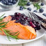 Baked salmon fillet with blueberry and rosmarin sauce on white plate, square format Stock Images