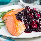 Baked salmon fillet with blueberry and rosmarin sauce on white plate, square format Stock Photography