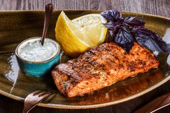 Baked salmon fillet with cheese sauce, basil and lemon on plate on wooden background. Hot fish dish. Top view stock photos