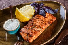 Baked salmon fillet with cheese sauce, basil and lemon on plate on wooden background. Hot fish dish. Top view. Baked salmon fillet with cheese sauce, basil and stock image