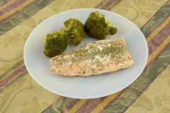 Baked salmon fillet with dill and steamed broccoli on plate Royalty Free Stock Photos