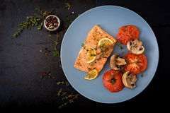 Baked salmon fish fillet with tomatoes, mushrooms and spices. royalty free stock photography