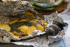 Baked salmon fish in foil. Tasty dish, cooked with potatoes and dill. stock images