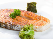 Baked salmon with fresh green broccoli on plate Royalty Free Stock Images
