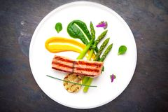 Baked salmon garnished with asparagus. Italian restaurant. Menu. Free space for text stock photography