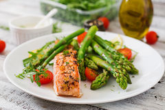 Baked salmon garnished with asparagus. And tomatoes with herbs royalty free stock photo