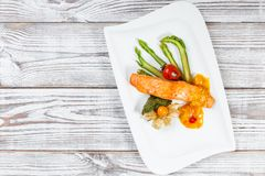 Baked salmon garnished with physalis, asparagus, tomatoes with herbs on wooden background. royalty free stock photo