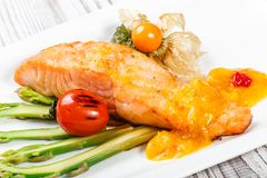 Baked salmon garnished with physalis, asparagus, tomatoes with herbs on wooden background. royalty free stock photography