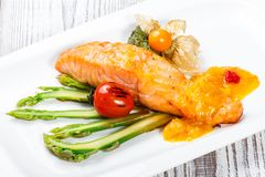 Baked salmon garnished with physalis, asparagus, tomatoes with herbs on wooden background. Hot fish dish. Top view stock photo