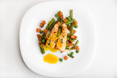 Baked salmon with green beans, carrots, green peas, thyme and orange sauce on a white plate Royalty Free Stock Photo
