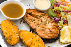 Baked salmon with hot dip and salad Royalty Free Stock Photos