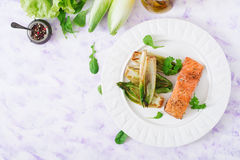 Baked salmon with Italian herbs and garnished with chicory. Stock Image
