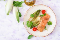 Baked salmon with Italian herbs and garnished with chicory. Stock Photo