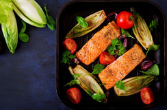 Baked salmon with Italian herbs and garnished with chicory. Royalty Free Stock Photo