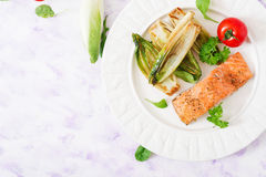 Baked salmon with Italian herbs and garnished with chicory. Royalty Free Stock Photography