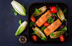 Baked salmon with Italian herbs and garnished with chicory. Stock Photos