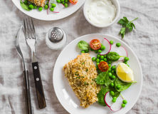 Baked salmon with lemon bread crust and fresh vegetable salad with peas, spinach, radishes and cherry tomatoes. Royalty Free Stock Photo