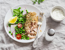Baked salmon with lemon bread crust and fresh vegetable salad with peas, spinach, radishes and cherry tomatoes. Royalty Free Stock Photos