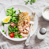 Baked salmon with lemon bread crust and fresh vegetable salad with peas, spinach, radishes and cherry tomatoes. Stock Image