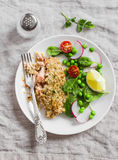 Baked salmon with lemon grain crust and fresh spinach, radishes, peas and tomatoes salad in white plate on gray surface. Stock Photo