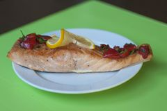 Baked salmon with lemon in a green background stock photos