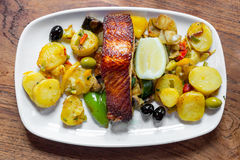 Baked salmon meat with potatoes and vegetables on a white plate in a restaurant stock images