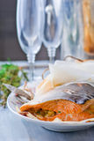 The baked salmon in parchment. A bottle of champagne and glasses Stock Image