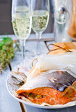 The baked salmon in parchment. A bottle of champagne and glasses Stock Images