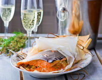 The baked salmon in parchment. A bottle of champagne and glasses Stock Photo