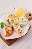 Baked salmon with parmesan and herbs, lemon and sauce. Fish with cheese on white plate. Royalty Free Stock Photos