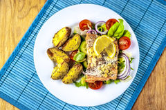 Baked salmon on salad with potatoes from above. Above, background, baked, blue, cherry, cooked, cuisine, dinner, dish, eating, fillet, fish, food, freshness Stock Images