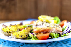 Baked salmon on salad with potatoes. On white plate Royalty Free Stock Photos