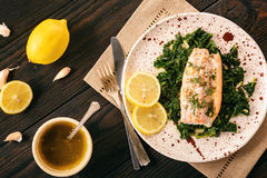 Baked salmon served on stewed spinach with lemon butter sauce. Royalty Free Stock Photography