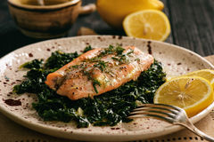 Baked salmon served on stewed spinach with lemon butter sauce. Baked salmon served on stewed spinach with lemon butter sauce Stock Photos