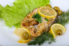Baked salmon steak. With lemon and olives Royalty Free Stock Image