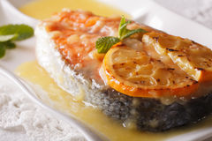 Baked salmon steak with orange sauce and mint close-up. horizont Stock Images