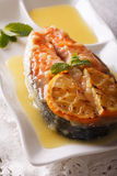 Baked salmon steak with orange sauce and mint close-up. Vertical Stock Photos