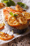 Baked salmon steak with oranges closeup on baking paper. Vertica Stock Photo