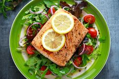 Baked salmon steak with tomato, onion, mix of green leaves salad in a plate. healthy food Stock Photo