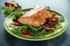 Baked salmon steak with tomato, onion, mix of green leaves salad in a plate. healthy food.  stock images