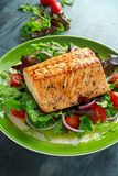 Baked salmon steak with tomato, onion, mix of green leaves salad in a plate. healthy food Stock Photos