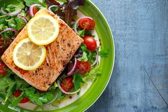 Baked salmon steak with tomato, onion, mix of green leaves salad in a plate. healthy food Stock Photography