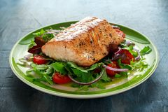 Baked salmon steak with tomato, onion, mix of green leaves salad in a plate. healthy food stock images