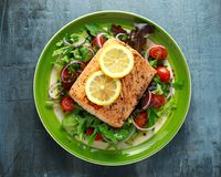 Baked salmon steak with tomato, onion, mix of green leaves salad in a plate. healthy food royalty free stock photos