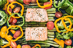 Baked salmon and vegetables on baking tray. Two pieces of fillet of baked salmon on green asparagus, pepper, cherry tomatoes and broccoli on baking tray stock photo