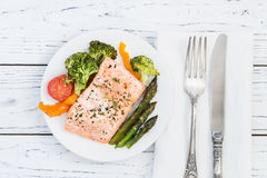Baked salmon with vegetables on plate. White wooden table Stock Photography