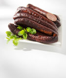 Baked sausage. On a plate on a white background royalty free stock photography