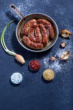 Baked sausages in a frying pan with the place for inscription. Stock Photography